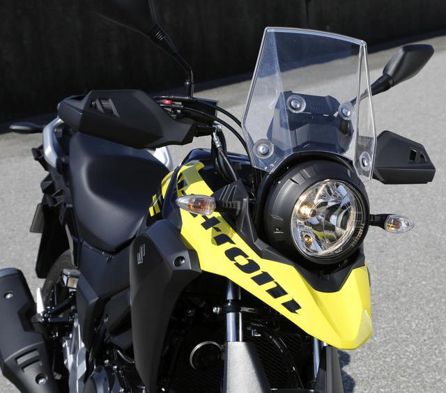 画像: Vストロームシリーズの統一イメージを持つ丸目ヘッドライト+クチバシフロントフェンダー。ヘッドライトデザインはタフギアっぽい遊びのあるデザインで、スクリーンは小ぶりながら整流効果の高いもの。ナックルガードも標準装備。