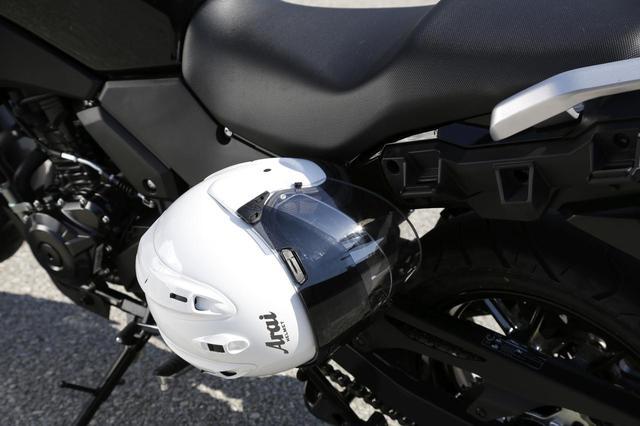 画像: ヘルメットホルダーは外部独立型でなく、シートを外して現われるフックに、ストラップのDリングやワイヤーを使ってホールドするタイプ。左右の同じ位置で合計2個のヘルメットを取り付けることができる。