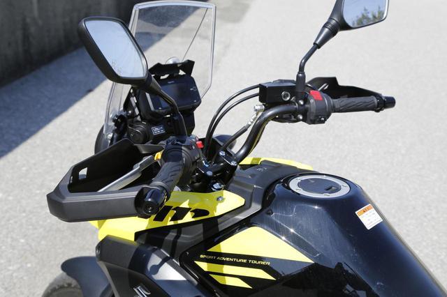 画像: ハンドルはかなりのプルバック形状で、快適なライディングポジションをとれる。ハンドガードとナックルカバーを標準装備しているのもオーナーやファンに好評な点だ。ハンドルスイッチにはハザードランプスイッチを標準装備する。