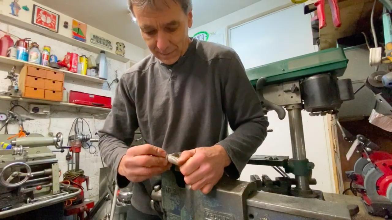 画像: バイスにくわえられたスプリングの、反対側端部をえいやっ! と手で曲げて、生じたスプリングの隙間にワッシャーを挟んでいきます・・・。 www.youtube.com