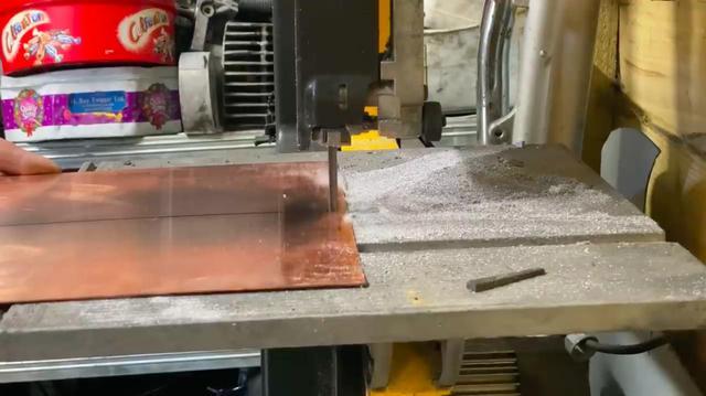 画像: 材料となる銅板をバンドソーで切断します・・・。スピード調整に注意しましょう。 www.youtube.com