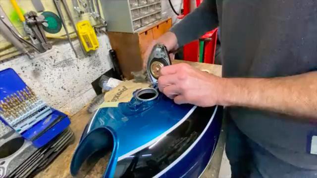 画像: 塗装した燃料タンクに、新しいフィラーキャップを取り付けます。穴位置合わせや養生、ハンマーなどの工具の使い方がとても参考になります。 www.youtube.com