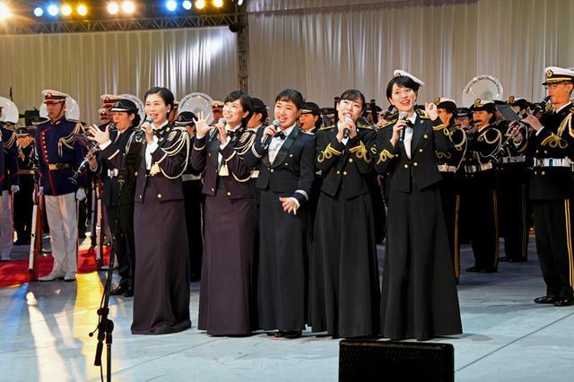 画像: 音楽隊の演奏で美しい歌声を披露する左から  松永美智子3陸曹、鶫真衣3陸曹、森田早貴1空士、中川麻里子3海曹、三宅由佳莉3海曹、の女性5人