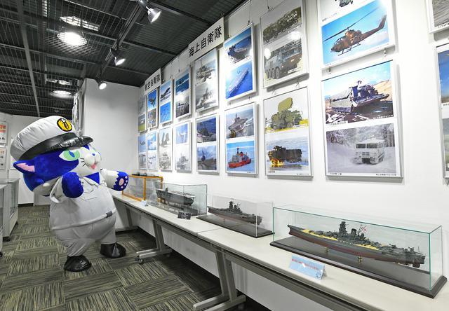 画像: 自衛隊の装備品や災害派遣活動の写真パネル、旧海軍の「大和」「赤城」などの艦船模型も展示されている
