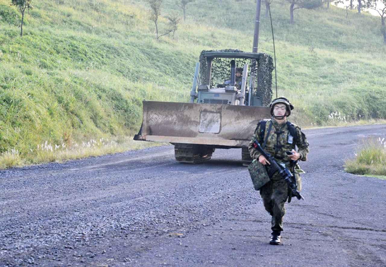 画像: 障害処理現場へ前進する第15施設中隊の小隊長とドーザー