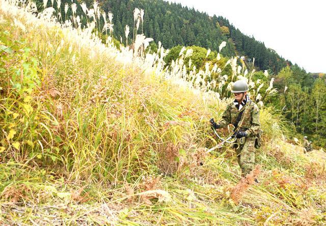画像: 斜度のある現場で懸命に作業する隊員