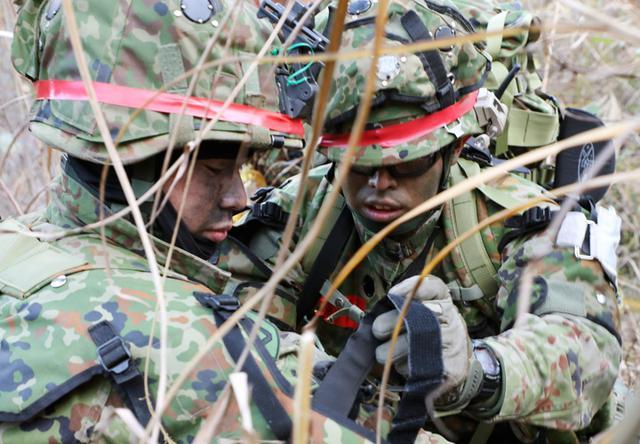 画像: 負傷者に対し第一線救護にあたる衛生小隊隊員