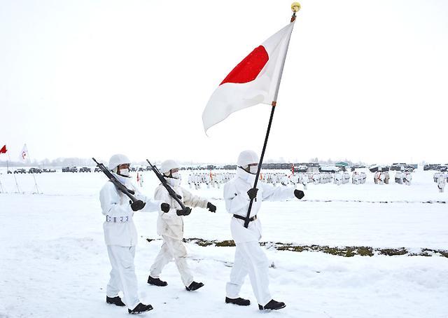 画像: 国旗とともに前進する隊員