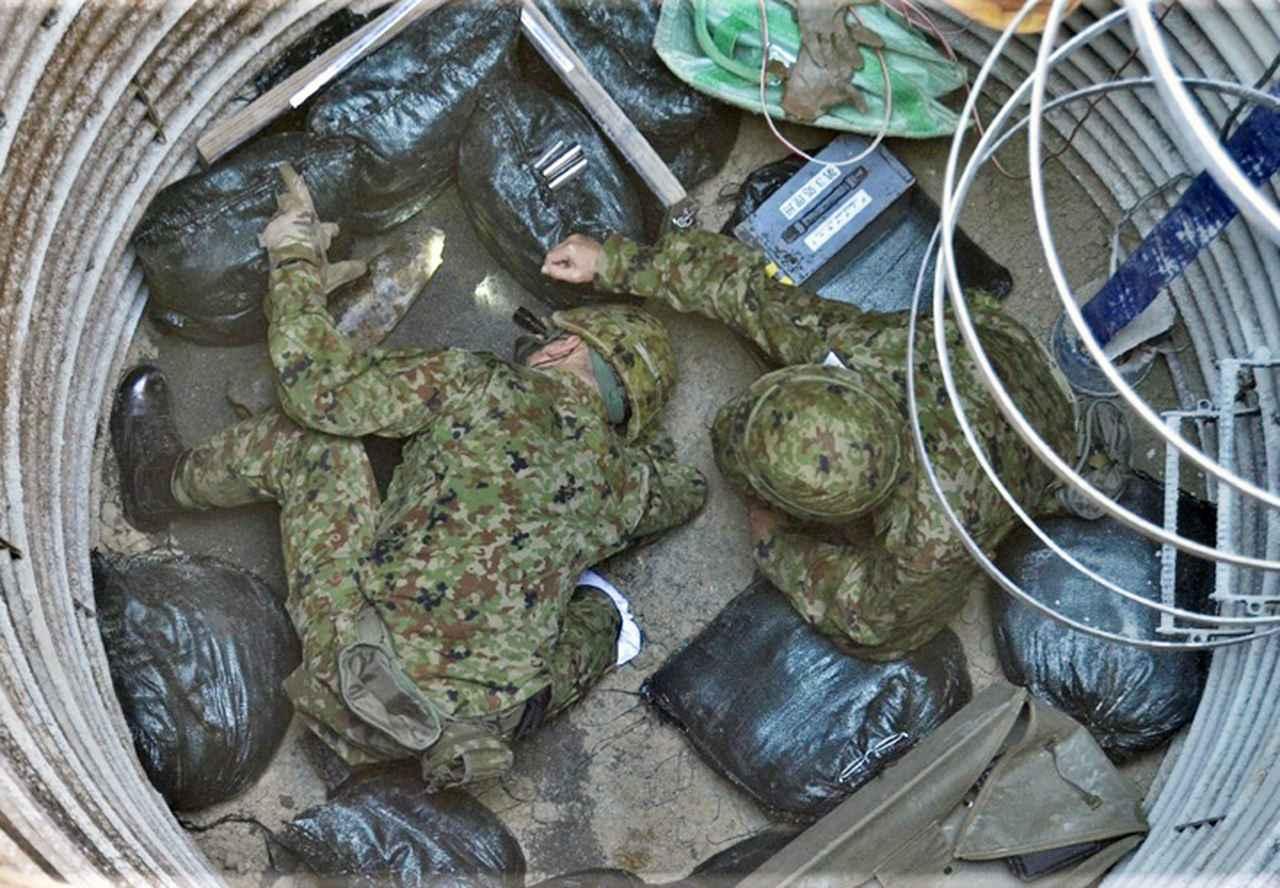 画像: 信管を確認する隊員