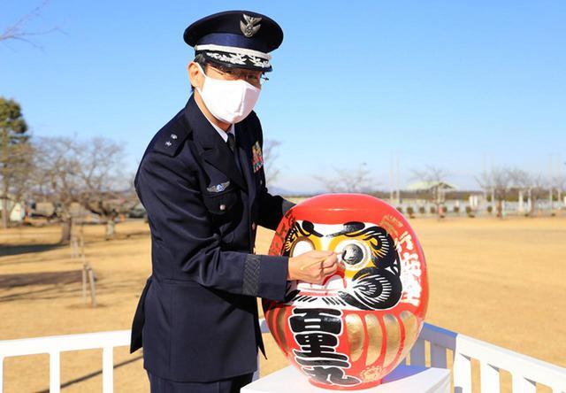 画像: 安全だるまに目を入れる基地司令