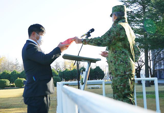 画像: 駐屯地朝礼における駐屯地司令より表彰を受ける西野技官