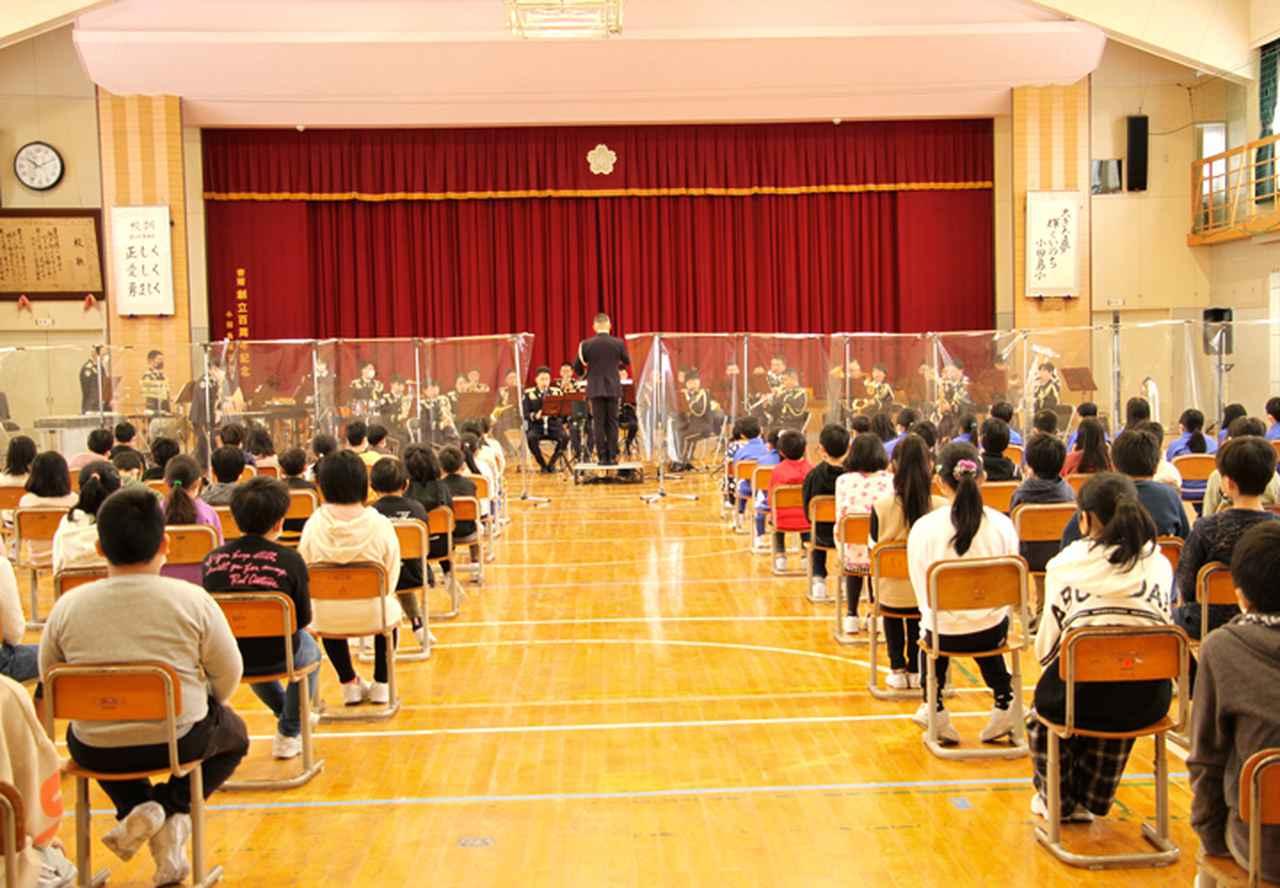 画像: 音楽隊と生徒の間に飛沫防止対策のパーティションを設置し演奏する音楽隊