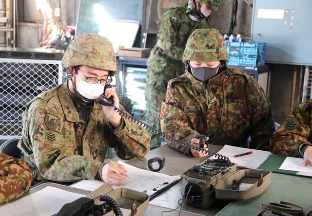 画像: 無線により対空情報を傍受・記録する隊員たち