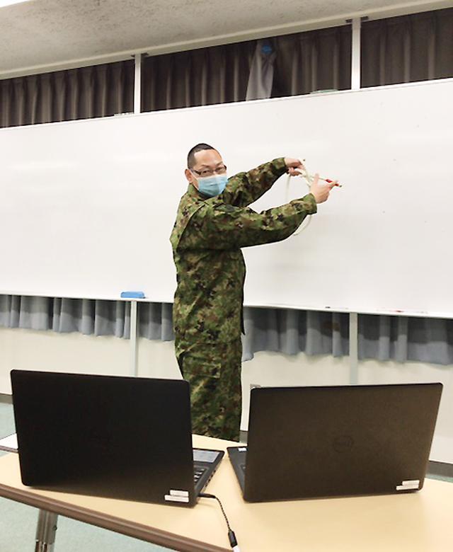 画像: ロープ結索を実演中の赤間広報官