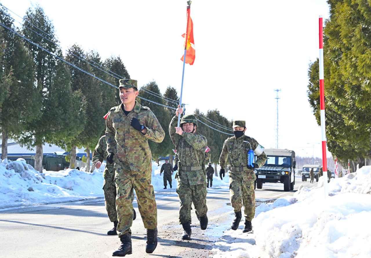 画像: 中隊旗を高く掲げながら前進