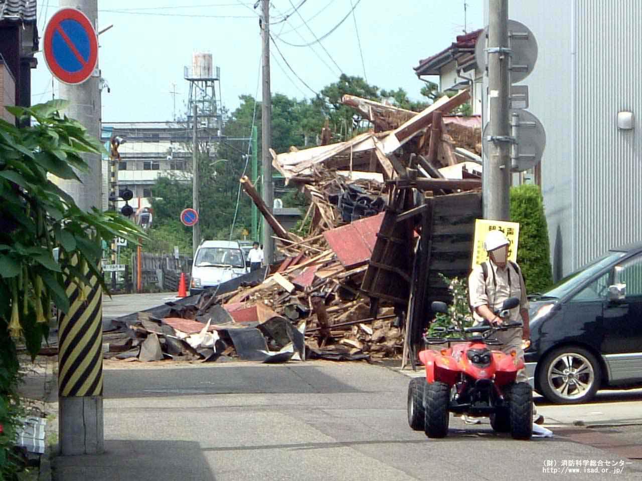 画像: 道路に倒れた家(新潟中越沖地震) 出典:消防庁ホームページ www.fdma.go.jp