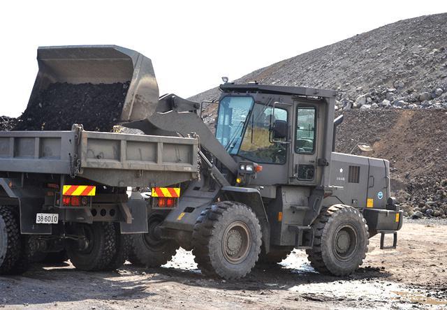 画像: バケットローダーによる骨材の積載 2月に準備した骨材を積込み現場へ輸送(393E)