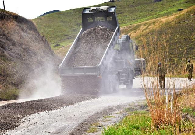 画像: 走行しながら砕石を散布する特大型ダンプ