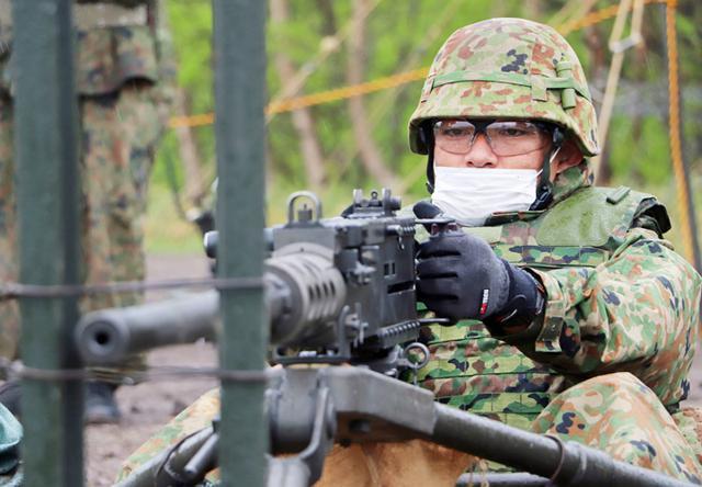 画像: 12.7ミリ重機関銃により狙いを定める隊員