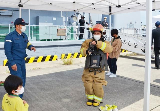 画像: 防火衣装着体験する見学者
