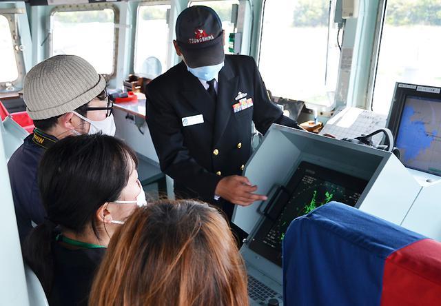 画像: 航海機器の説明を受ける見学者