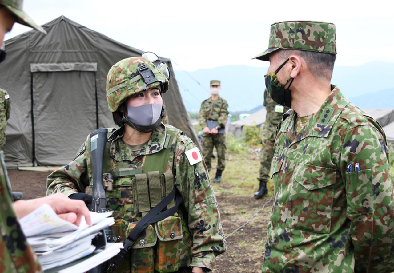画像: 総隊司令部幕僚長の牛嶋陸将(右)から激励される穴澤1陸曹(左)