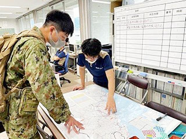 画像: 陸上自衛隊西部方面特科連隊(北熊本)の隊員が、連絡員として自治体関係者と調整している様子 統合幕僚監部ツイッターから twitter.com