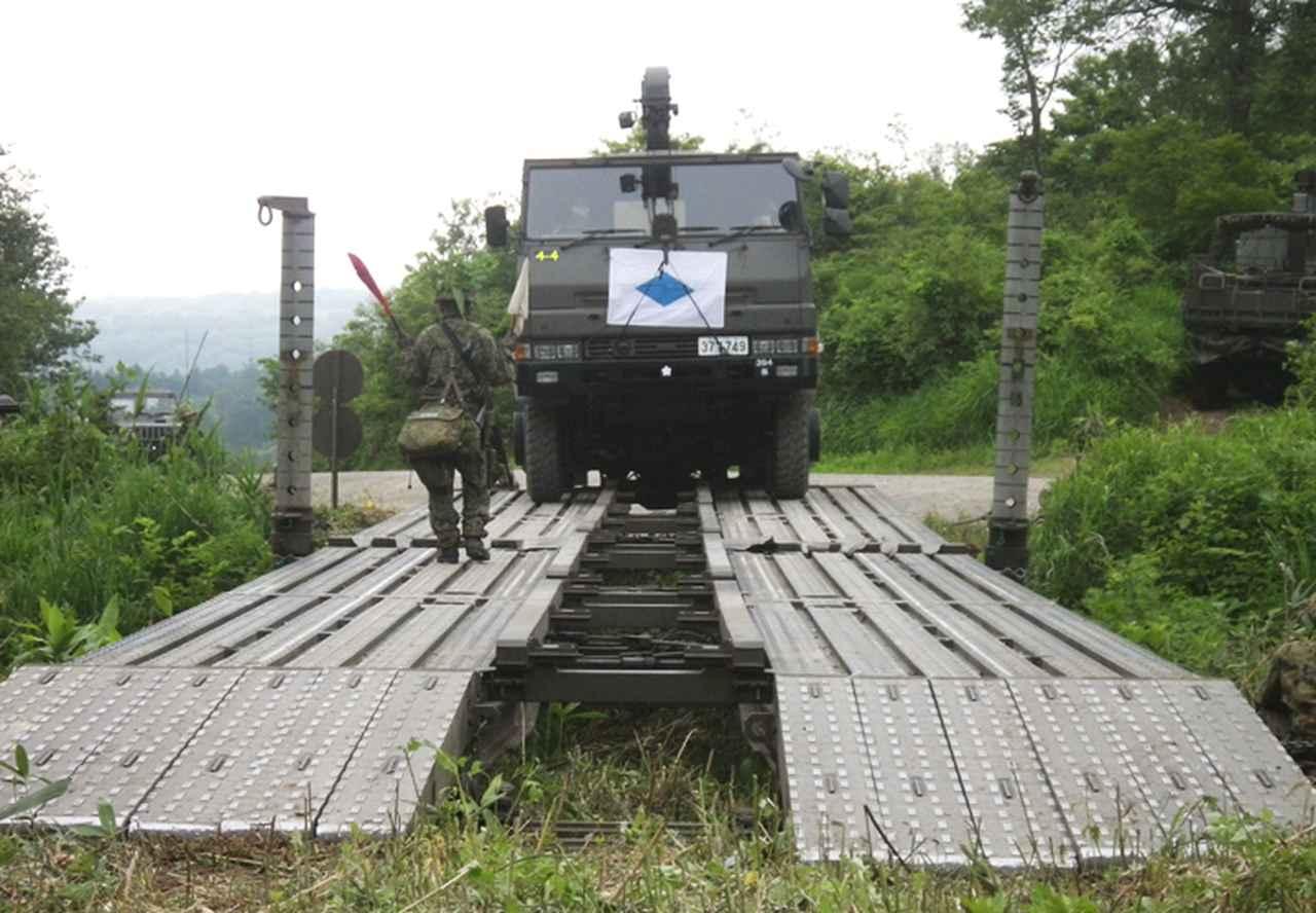 画像: 完成した架柱橋で誘導する隊員(394E)