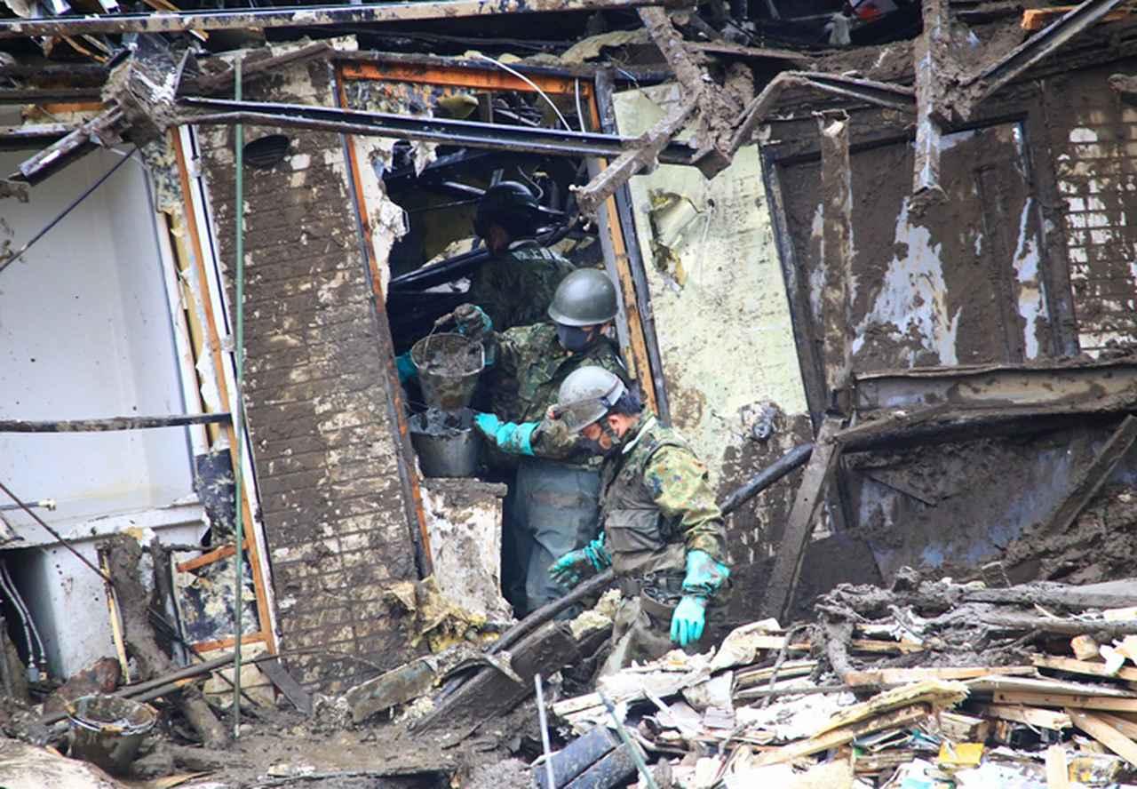 画像: 倒壊家屋からバケツリレーで土砂を搬出する隊員