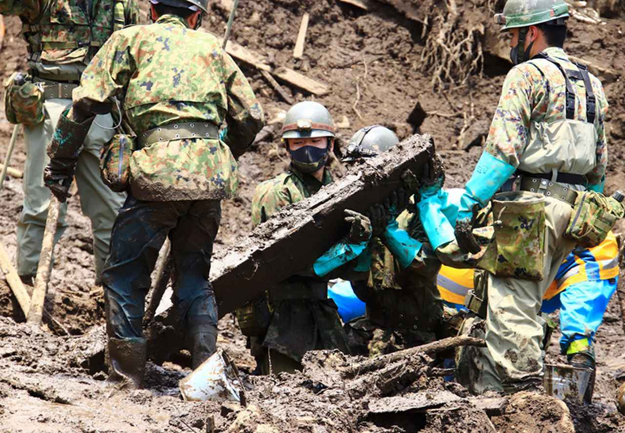 画像: 協力して重い木材を持ち上げる隊員