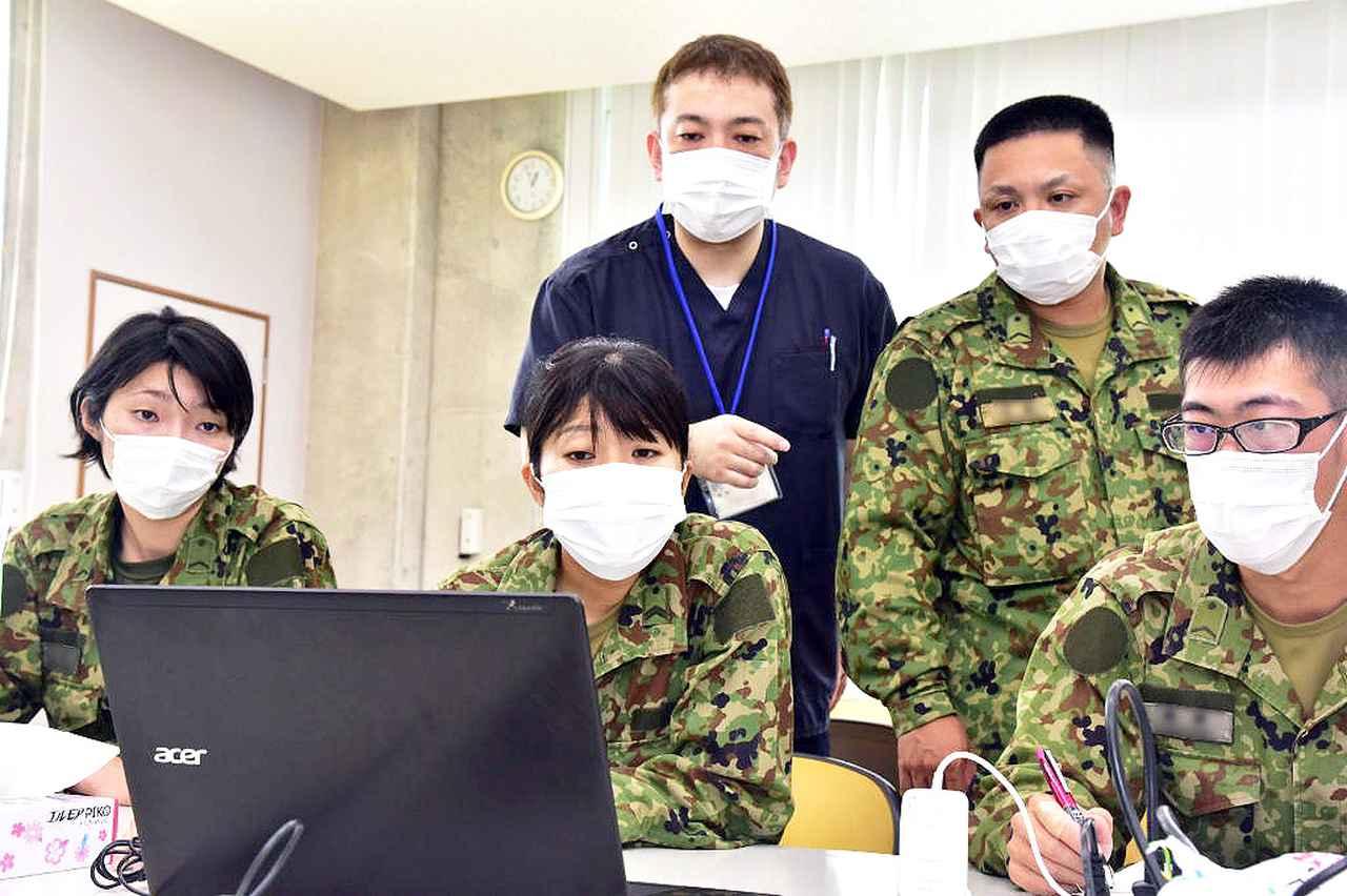 画像: 写真は、派遣隊員が沖縄県の職員と打ち合わせを行っている様子 統合幕僚監部ツイッターより twitter.com