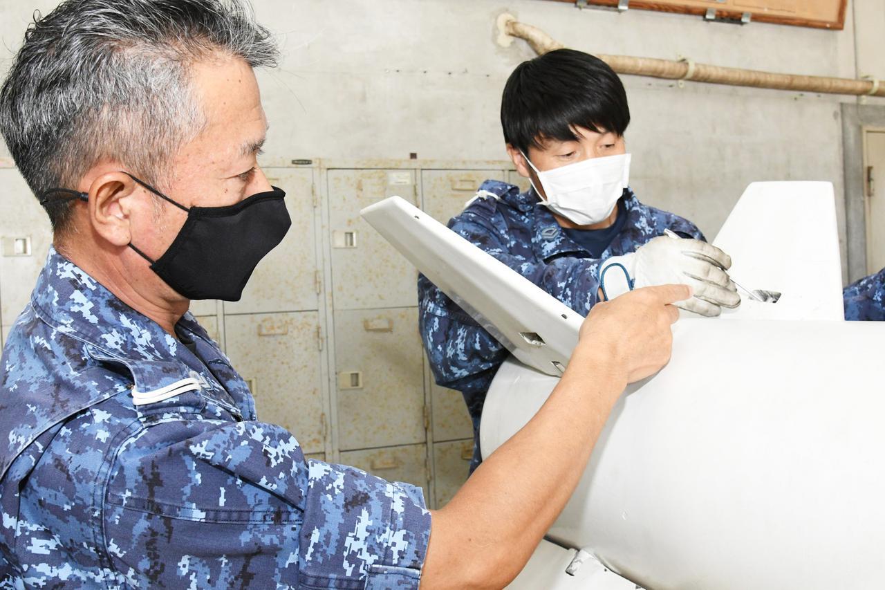 画像: 若い隊員に弾薬搭載訓練用のダミー弾の点検方法を教える和成2曹