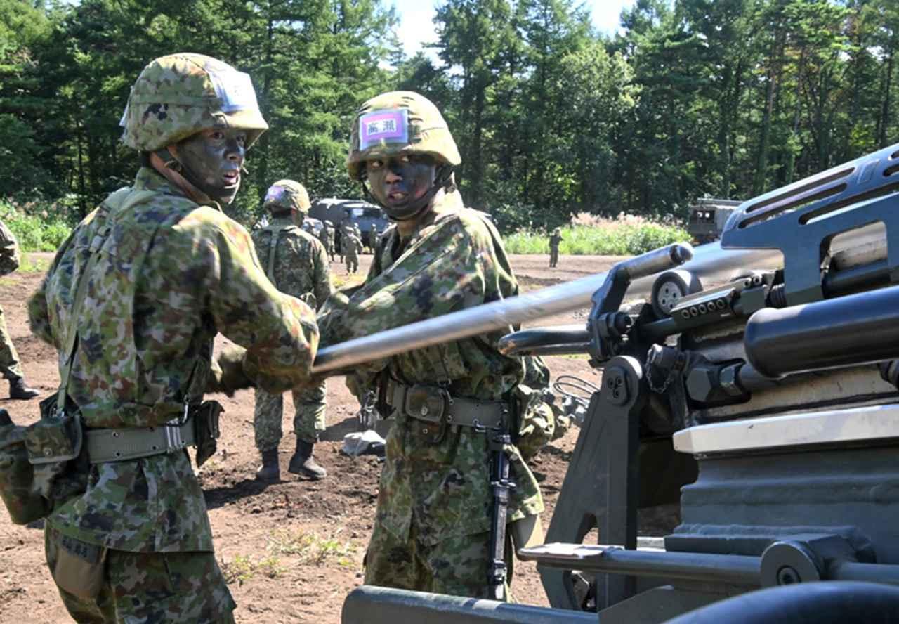 画像: 装填棒を使い砲弾(空砲)を込める