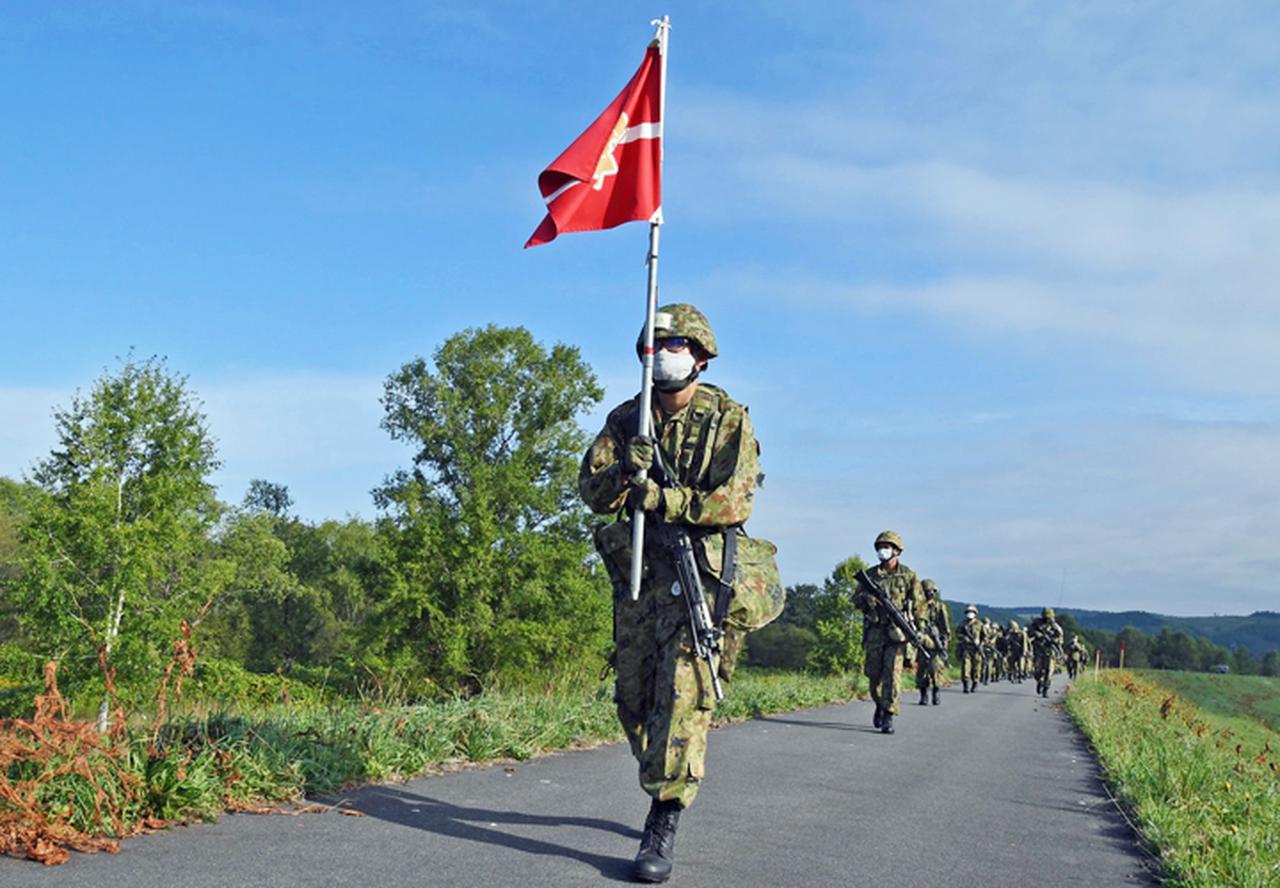 画像: 区隊旗を掲げ先頭を行進する旗手(新隊員)