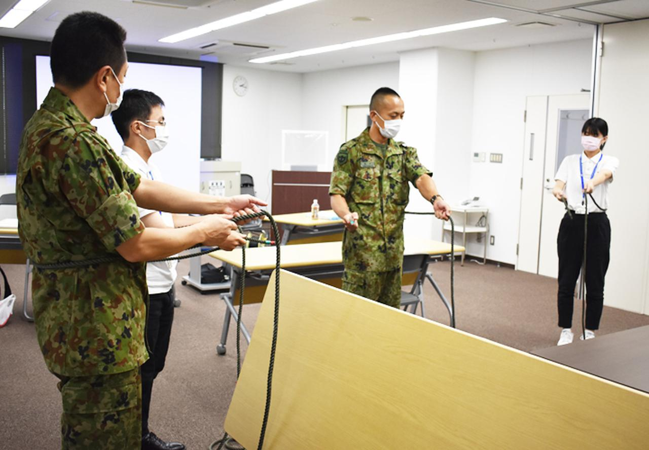 画像: ロープワークの指導 を受ける大学生