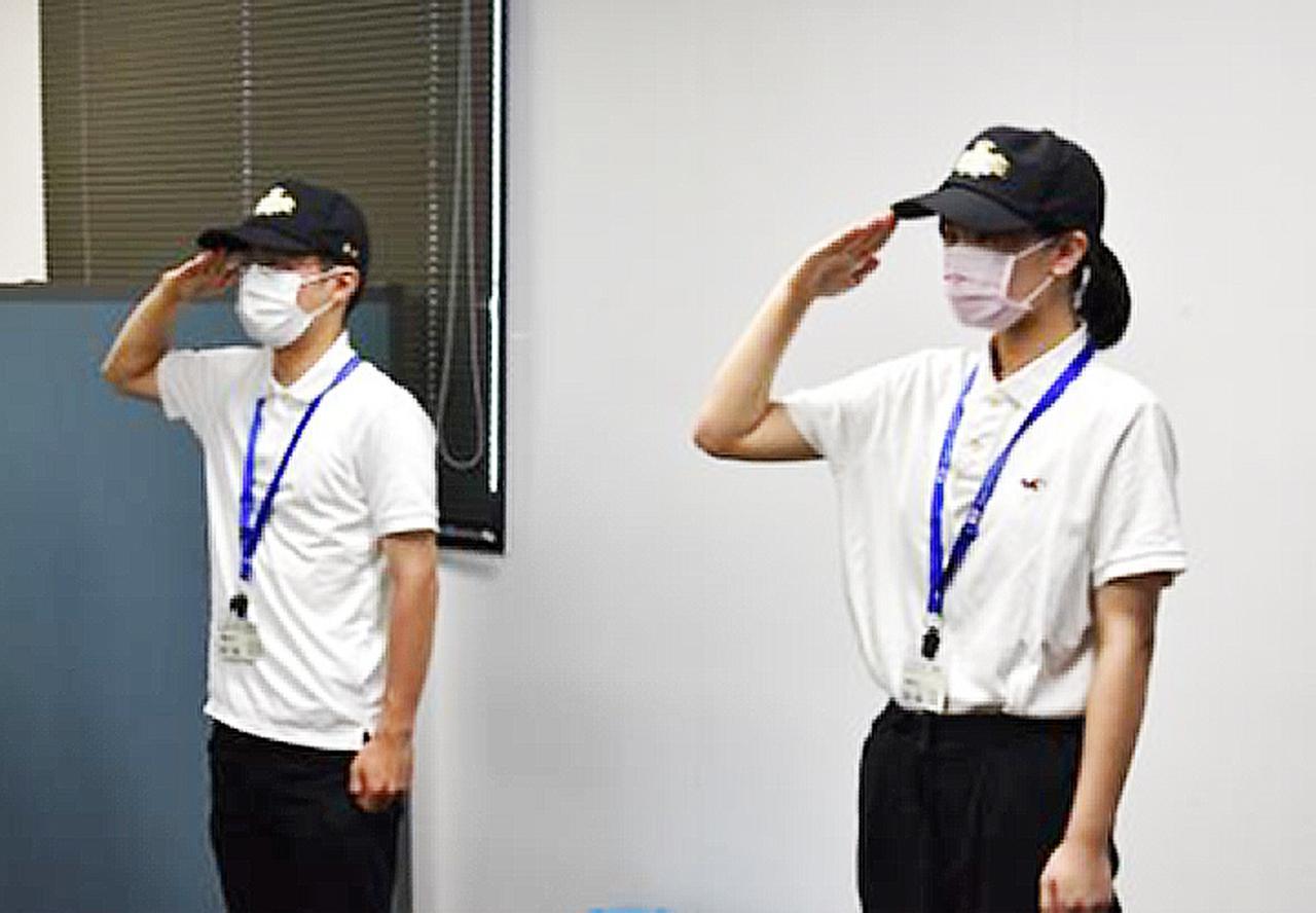 画像: 挙手の敬礼を練習 する 大学生
