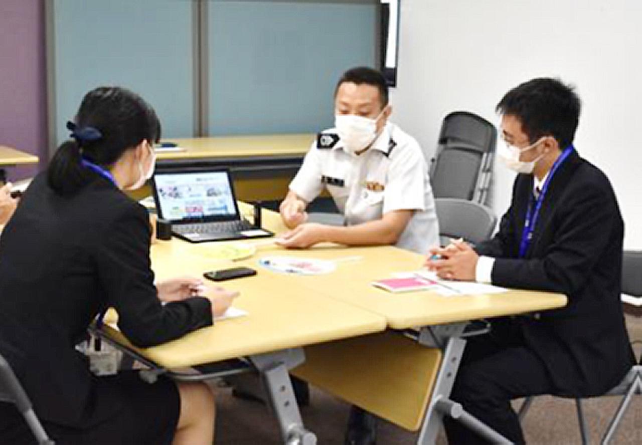 画像: 広報班の隊員から グッズ作成の説明を受ける大学生