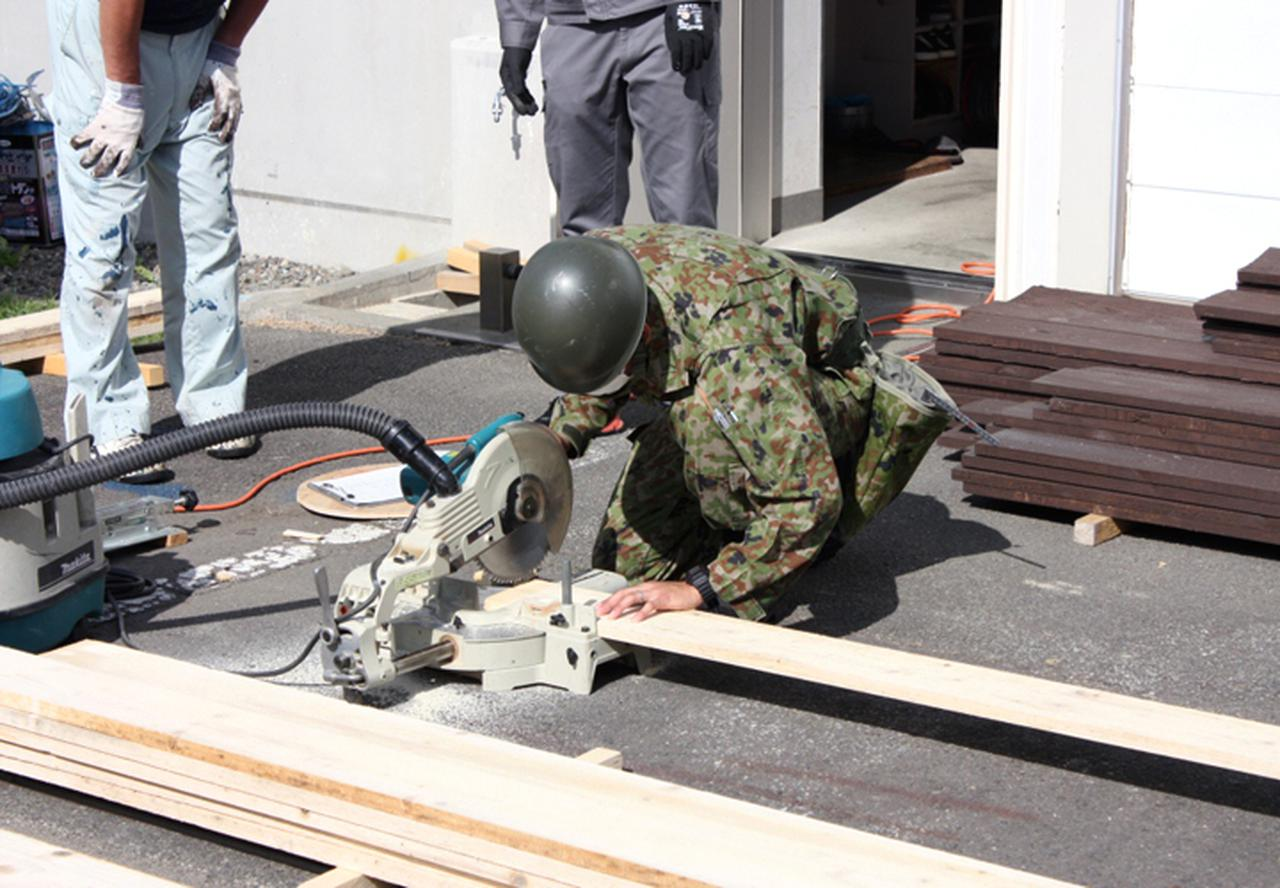画像: 丸のこで木材加工する隊員