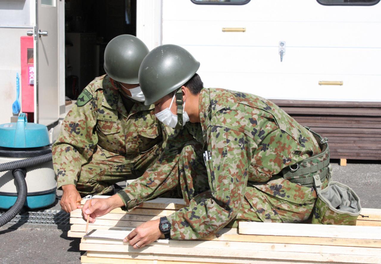 画像: 木材を経始する隊員
