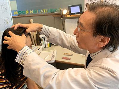 画像: 自律神経の治療点を指先で刺激する光武先生