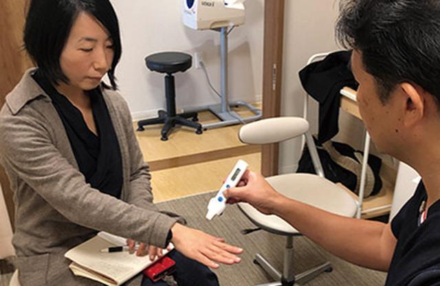 画像: 手の甲の体温を測る林先生。冷え症外来の診断はここから始まる