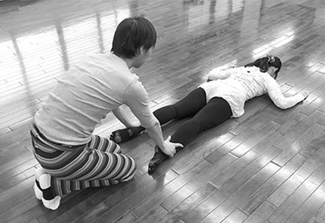 画像: フロアバレエを指導する佐々木先生。ふだんの生活でしている動作を床に寝て行う