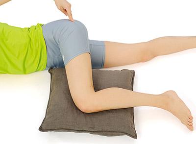 画像: 痛みがある場合は、ひざの下にクッションを入れる。