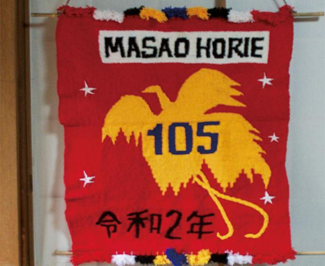 画像: 慰霊訪問をしているパプアニューギニアからは、誕生日のたびに年齢が刺繍された旗が贈られる。