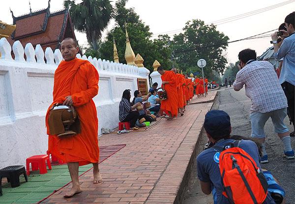 画像: 托鉢風景に観光客の撮影者が群がる。