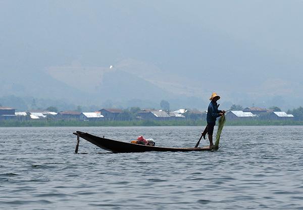 画像: オールを足で漕ぐ独特のインター族の漁。