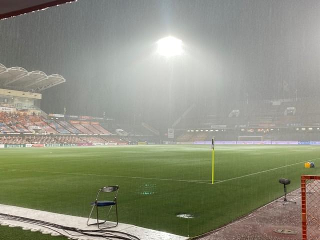 画像: 試合の中断中、激しい雨で表面が白くなるアイスタのピッチ