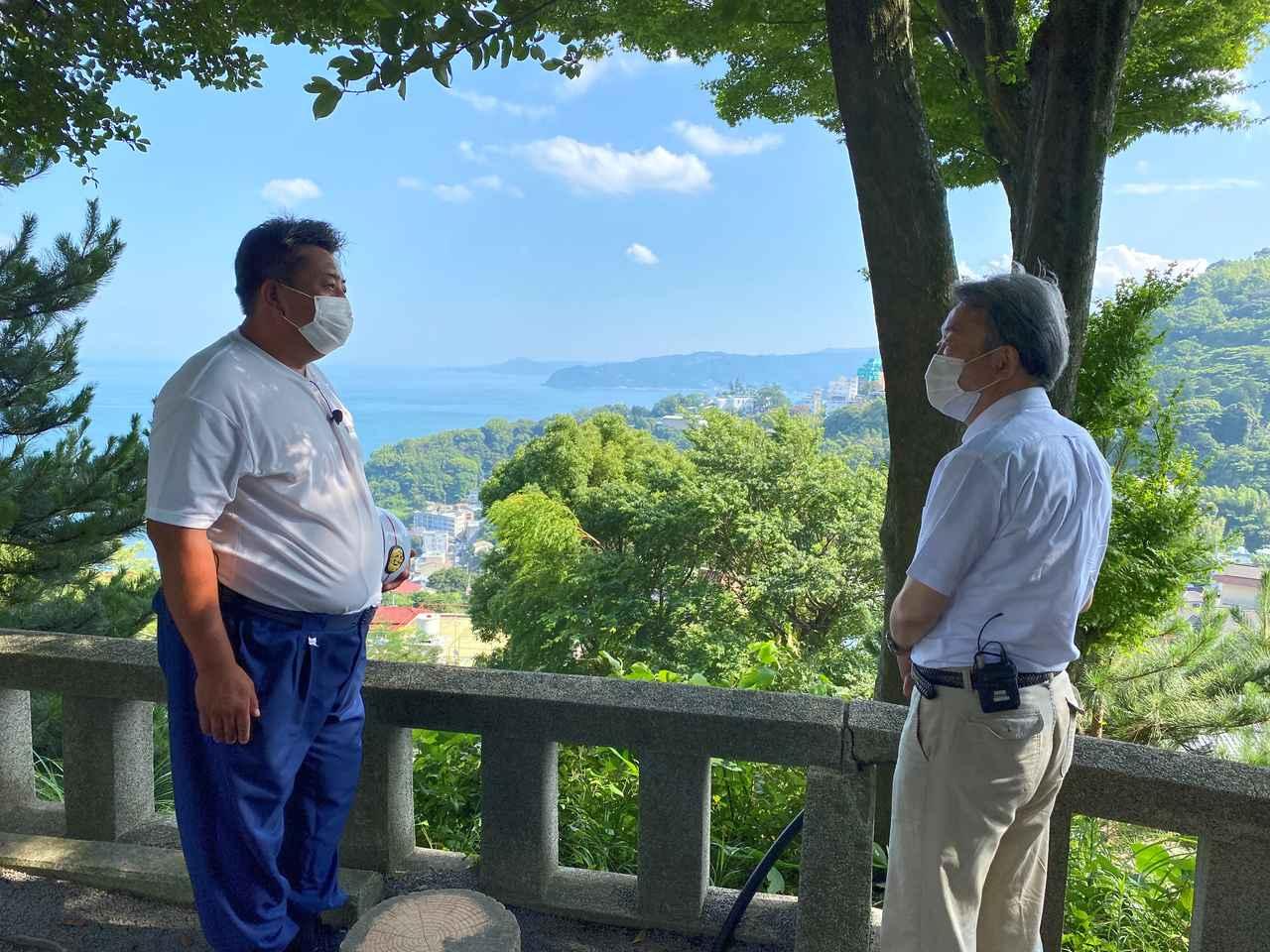 画像: 熱海市内の高台で、地元消防団員の松本早人さん(左)を取材する池上彰氏