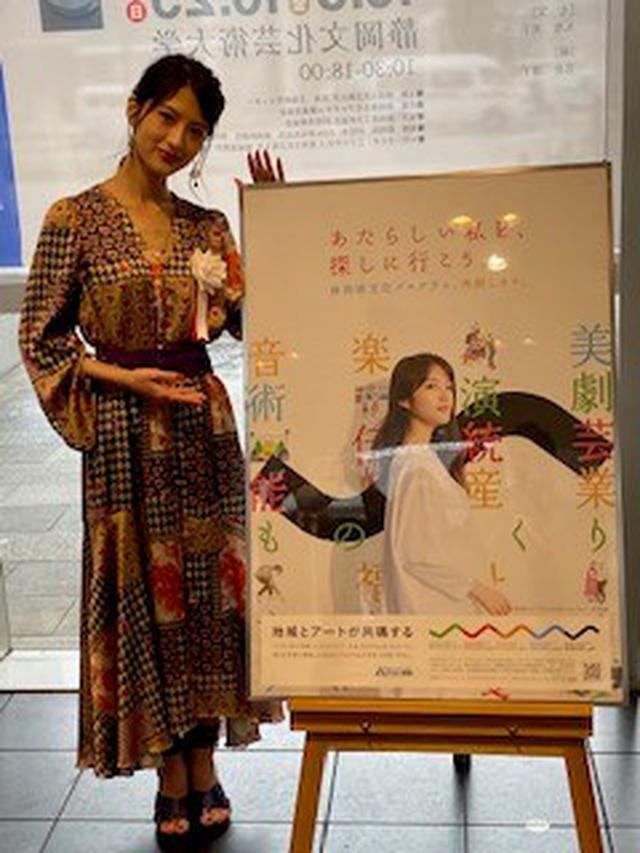画像: (ポスターを前にポーズをとる若月さん)