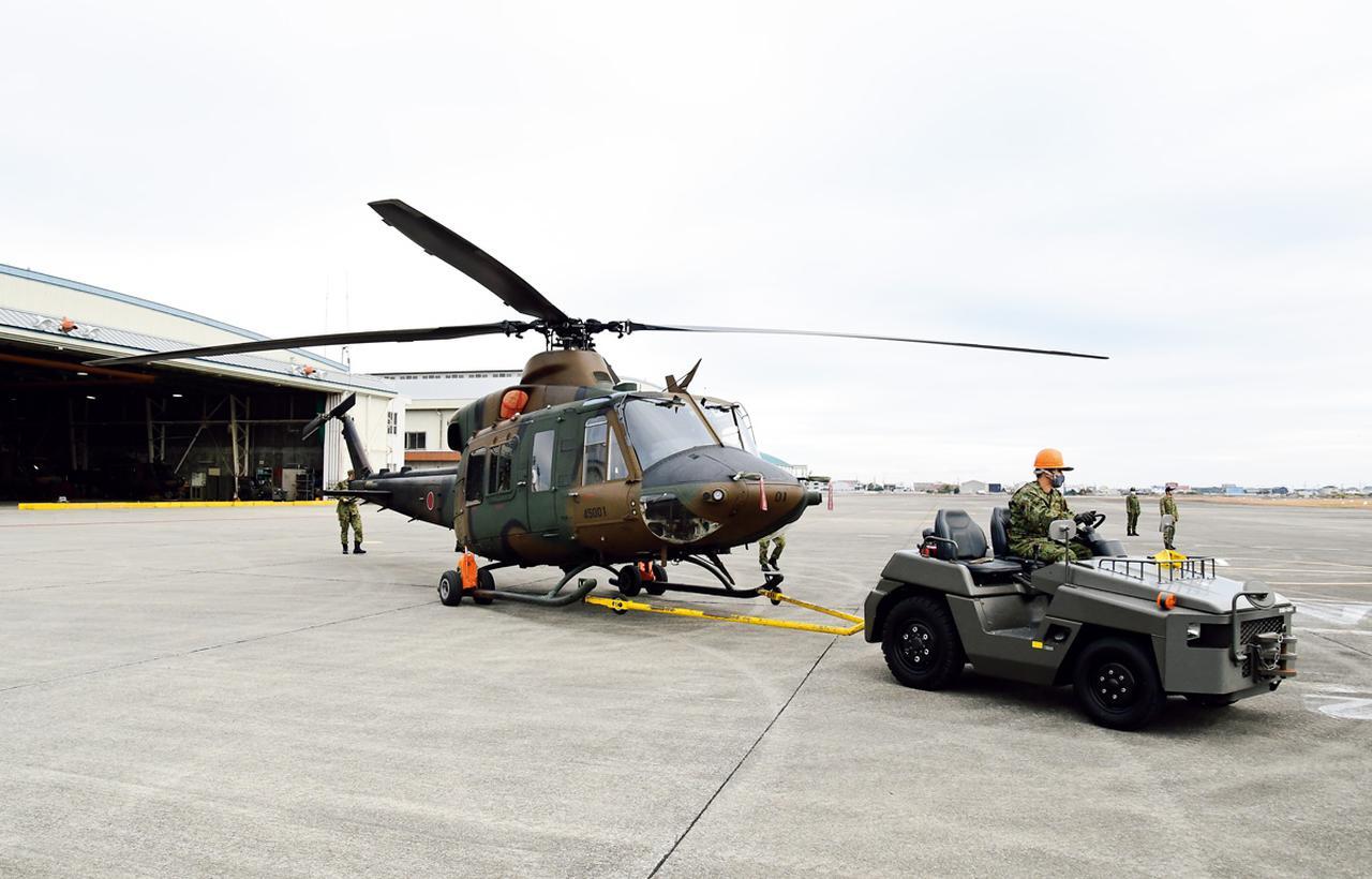 画像: 飛行試験に備え、格納庫から明野駐屯地の滑走路脇エプロンに引き出されるUH-X試験機。1機しかない試験機の扱いは、ほかの機体にもまして慎重に行われる